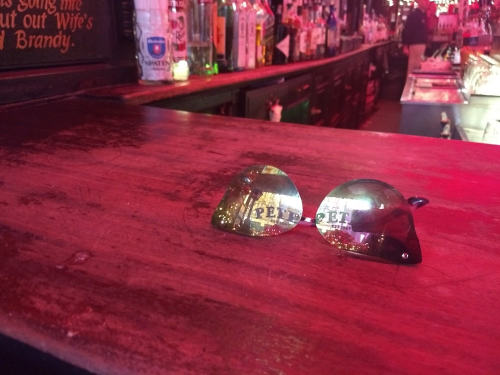 My glasses at the bar with the reflection of Pete's Tavern name