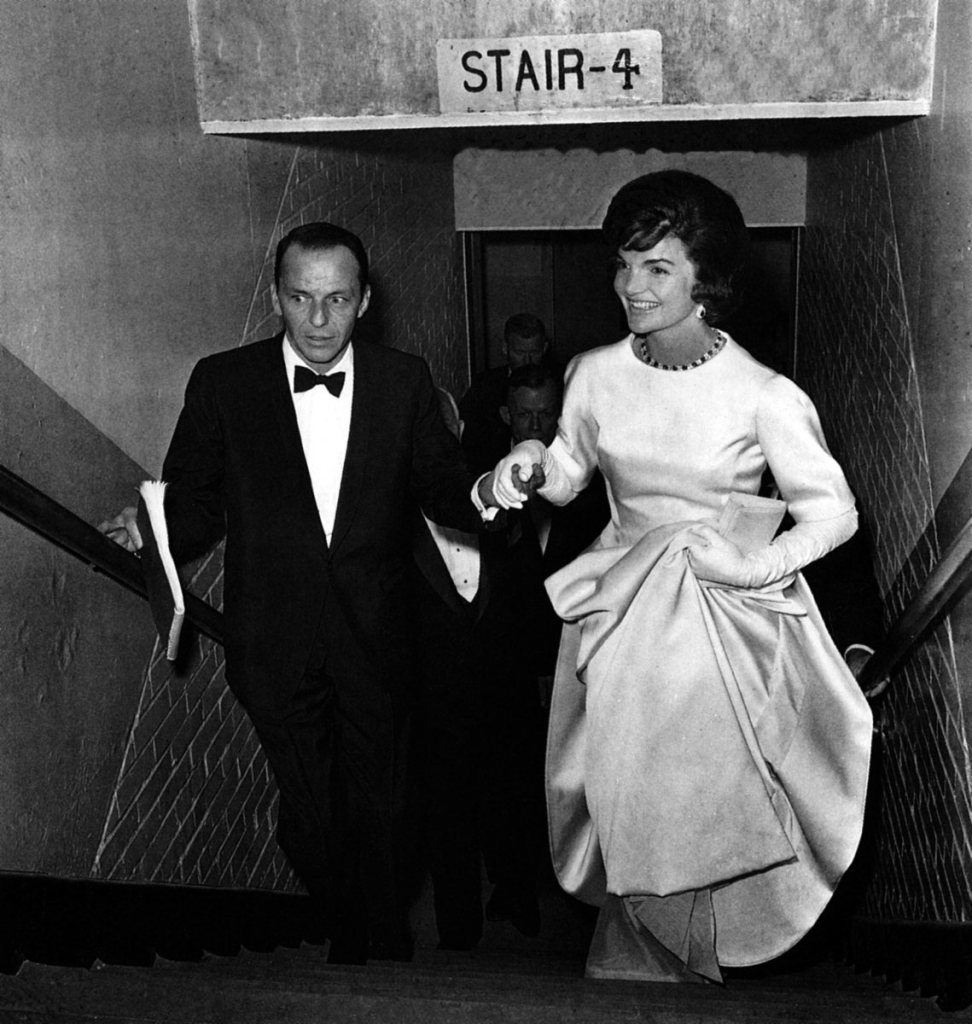 Frank Sinatra escorting Jackie Kennedy to her box at a gala,